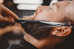 Close-up of barber shearing beard to man in barbershop