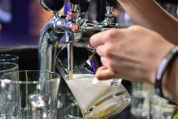close-up of barman hand at beer tap pouring a draught lager beer