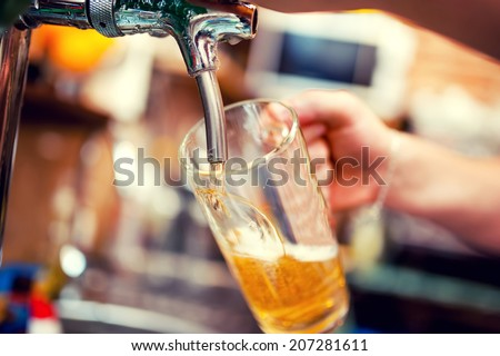 close-up of barman hand at beer tap pouring a draught lager beer #207281611