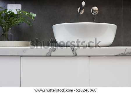 Close up of bathroom basin on a marble top vanity