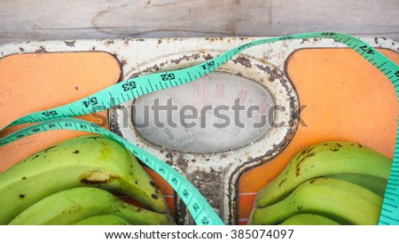 Close up of bathroom weight scale, measuring tape and green banana