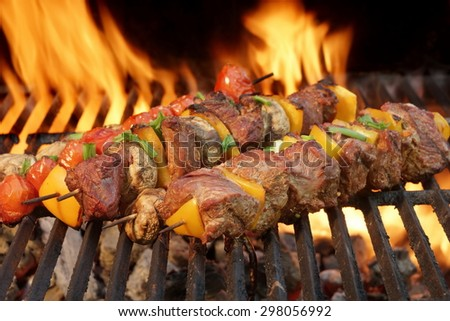 Close-up Of BBQ Tasty Cubed Beef Kebabs With Paprika Slice On The Flaming Charcoal Grill In The Background