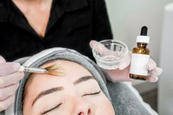 Close up of beautician (cosmetologist) applying chemical peel treatment on patient in a beauty spa, for skin rejuvenation, complexion and acne beauty treatments.