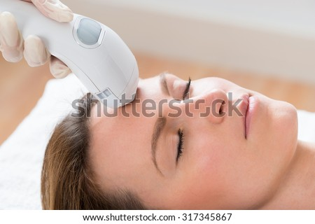 Close-up Of Beautician Giving Laser Epilation Treatment To Young Woman Face