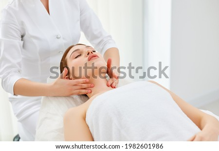 Close up of beautician or masseur doing myofascial or buccal head and face massage for young woman. Female patient lying at spa center, receiving anti aging beauty treatment. Skin rejuvenation concept Stockfoto ©