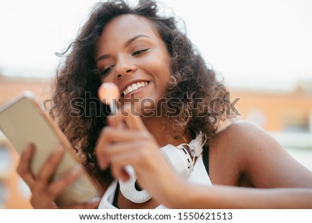 Close up of beautiful african woman outdoors using phone.