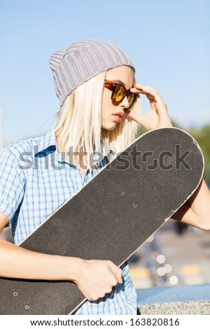 Close-up of beautiful blond girl in beanie hat skateboard adjusting her leopard sunglasses on sunny day in the street