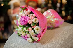 Close-up of beautiful delicate bouquet of peonies and roses decorated with branches of greenery wrapped in pink paper lies on table