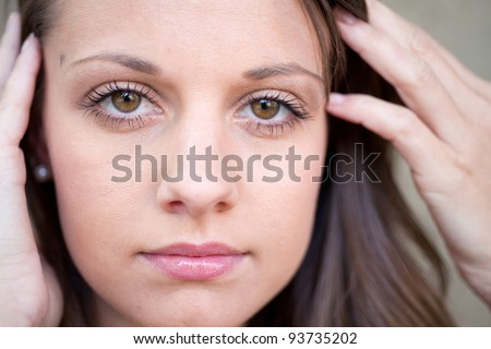 Close up of beautiful female face with hands close to her face