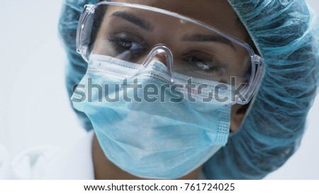 Close-up of beautiful female scientist face with security goggles, medicine #761724025