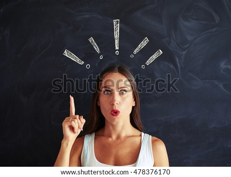Close-up of beautiful female who look like trying to pay your attention against school blackboard with chalk exclamation marks