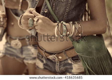 close up of beautiful hippie girls in denim clothes and boho accessories