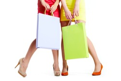Close-up of beautiful legs of shoppers with paperbags over white background
