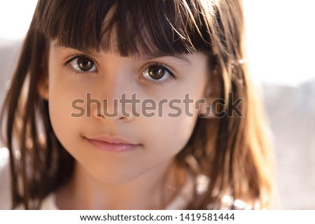 Close up of beautiful little brunette girl with big brown eyes look in camera smiling, portrait of cute preschooler child daughter posing making picture.