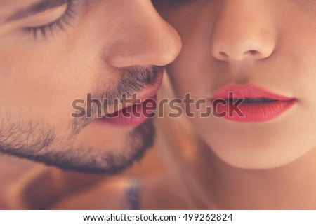 Close-up of beautiful passionate couple kissing while having sex