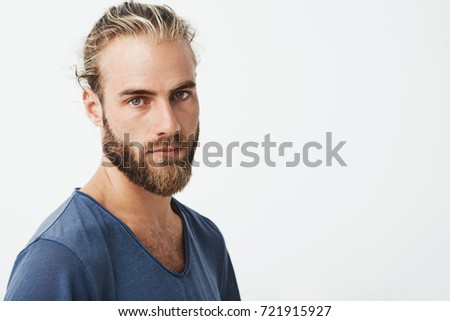 Close up of beautiful swedish man with stylish hairstyle and beard in blue t-shirt looking in camera with serious expression. #721915927