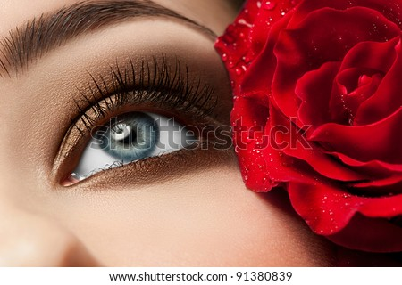 Close-up of beautiful woman eye with red rose and stylish makeup