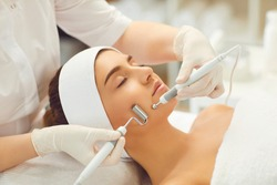 Close-up of beautiful woman face receiving facial microcurrent treatment with apparatus from therapist in beauty wellness salon. Using electrical impulses in cosmetology concept