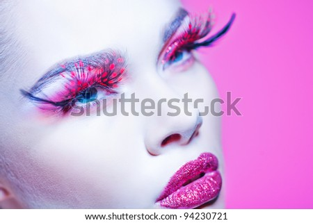 Close-up of beautiful woman face with Creative Fashion Art make up and eyelashes.  Studio