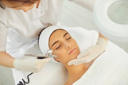 Close-up of beautiful woman getting procedure of oxygen therapy or jet peeling from cosmetologist with special equipment in beauty spa salon, top view.