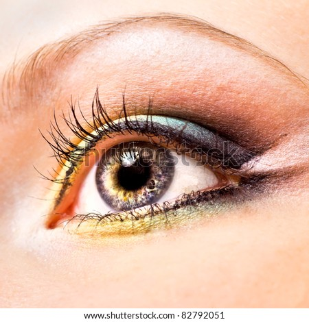 Close-up of beautiful womanish eye with yellow and green make-up