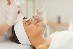 Close-up of beautiful womans forehead and face getting microcurrent treatment with special apparatus from therapist in beauty salon, side view. Using electrical impulses in cosmetology concept