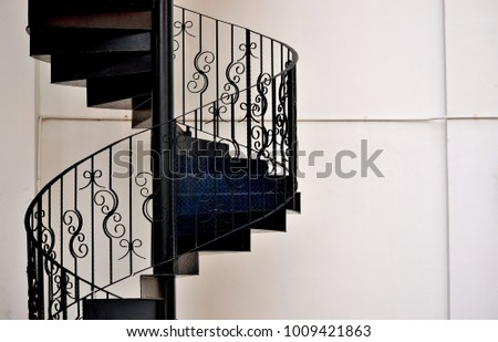 Close up of beautiful wrought iron exterior spiral staircase on the side of a shop house in Singapore with copy space for design\n