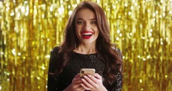 Close up of beautiful young charming  brunette woman in fancy outlook tapping and texting on the smartphone, chatting and getting good news in message so being very happy on golden shiny wall.
