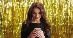 Close up of beautiful young charming Caucasian brunette woman in fancy outlook tapping and texting on smartphone, chatting and getting good news in message so being very happy on golden shiny wall.