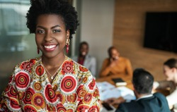 close up of beautiful young smiling professional black african business woman, coworkers hold a meeting in background