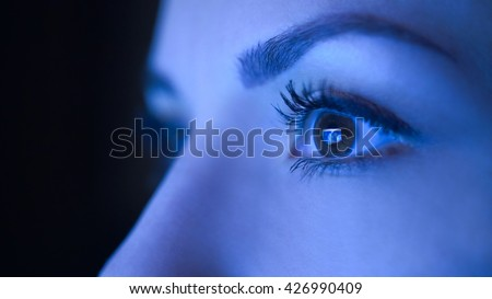 Close-up of beautiful young woman eyes looking at monitor, working with computer, laptop. Monitor blue light is reflected in her eyes. Evening woman freelancer working, shopping online, watch video.
