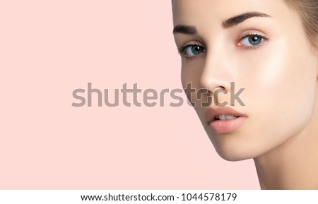 Close up of beautiful young woman's face with clean perfect skin. Portrait of beauty model with natural nude make up. Spa, skincare and wellness. Pink peach coral background, copyspace.