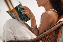 close up of beautiful young woman sitting in chair on beach and reading book