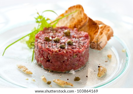 Close up of beef tartar with capers and small toasts. - stock photo