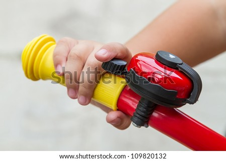 Close up of bicycle bell on handlebars and hand the child.