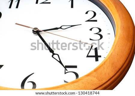 Close up of big round wall clock with wooden frame and golden second hand on white background
