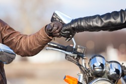 Close up of bikers hands in leather gloves with repay a salutation
