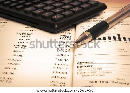 Close up of bills, calculator, pen, account statement