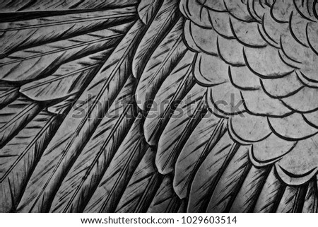 Close up of bird feathers etched on a grey metal surface. #1029603514