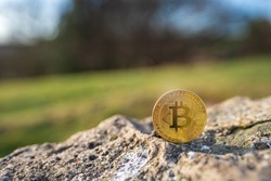 Close-up of Bitcoin on a stone outdoor with green natural background with copy space. Single physical metal gold shining BTC cryptocurrency coin. Environment impact of crypto mining concept