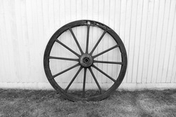 close up of black and white image of  large wooden cartwheel .  Round wheel with wood spokes and metal centre outside against fence panels