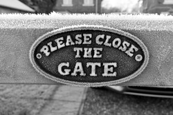 close up of black and white image Please close the gate sign, covered in frost, on a wooden gate.  Outside on a cold winters day