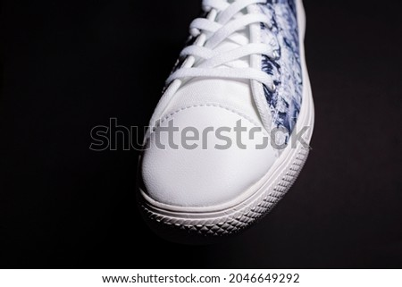 Close up of black and white shoe sneakers on black background.