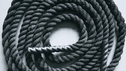 Close up of black battle rope on a gray backgound. Sport and fitness equipment. Functional training