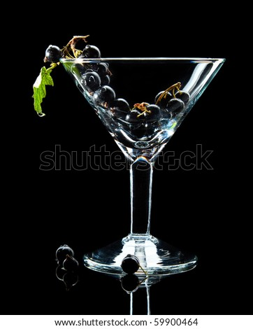 Close-up of black currant bunch in wineglass isolated over black