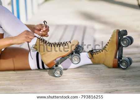 Close-up of black girl sitting on wooden floor puts on skates outdoors. Unrecognizable woman.