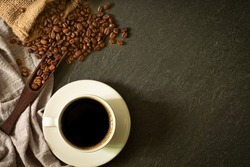 Close-up of Black hot coffee for morning with milk foam in white ceramic cup and napkin with coffee beans roasted in sack on dark table stone background. Top view, flat lay with copy space.