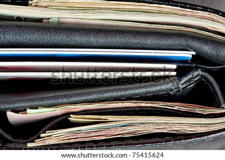 Close-up of black leather wallet with cards and money