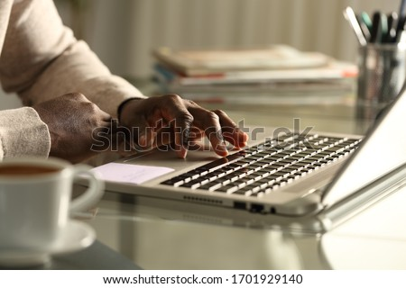 Close up of black man hand using touchpad on laptop on a desk at night Stock fotó ©