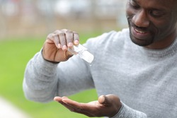 Close up of black man using hand sanitizer rub standing in a park
